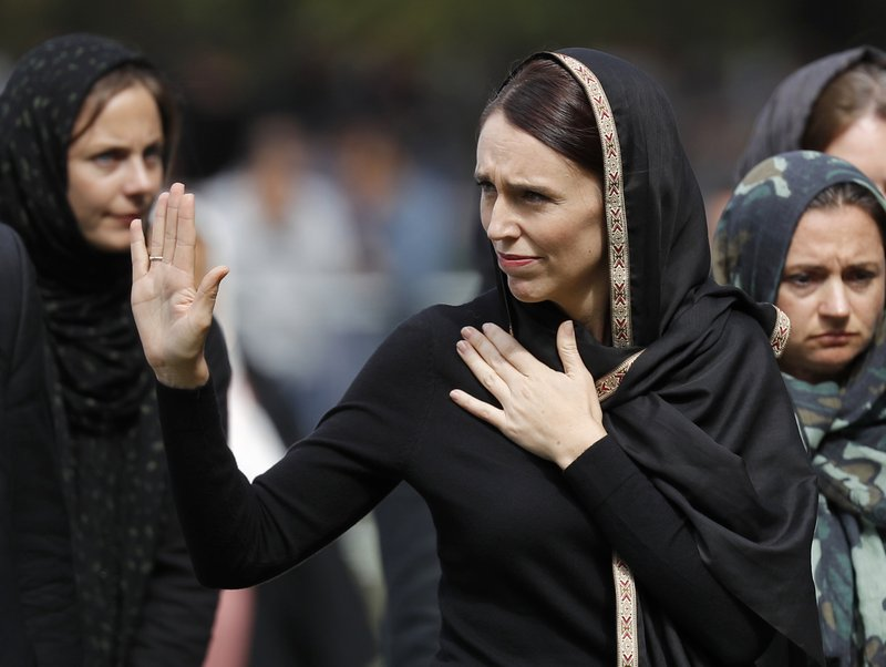 New Zealand Prime Minister Jacinda Ardern, center, waves as she leaves Friday prayers at Hagley Park in Christchurch, New Zealand, Friday, March 22, 2019. (AP Photo/Vincent Thian)