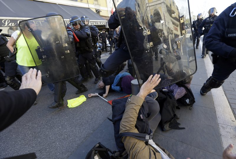 Police officers push demonstrators during a protest in Nice, southeastern France, Saturday, March 23, 2019. (AP Photo/Claude Paris)