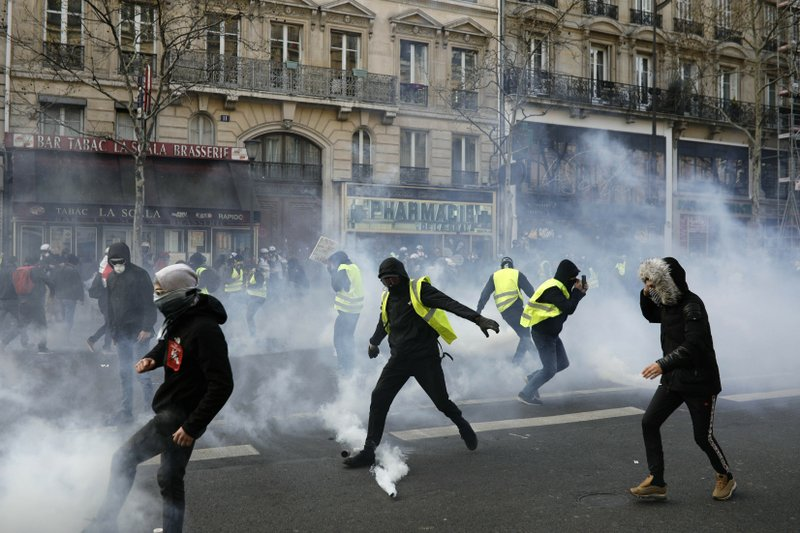 Teargas is used to disperse demonstratos during minor clashes with police in Paris, Saturday, March 23, 2019. (AP Photo/Kamil Zihnioglu)
