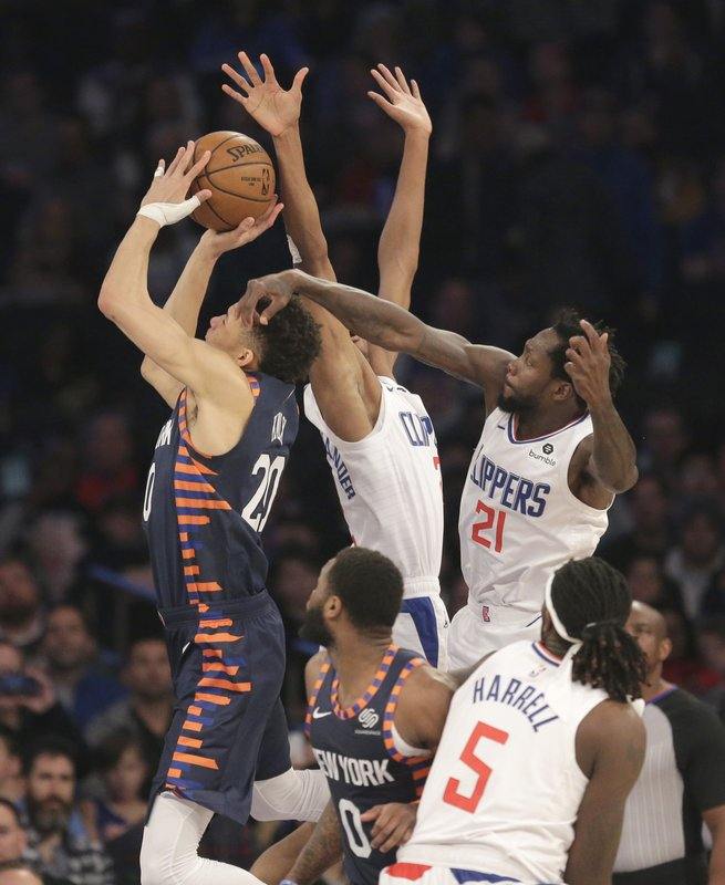 New York Knicks forward Kevin Knox (20), left, drives through Los Angeles Clippers defenders during the first half of an NBA basketball game, Sunday, March 24, 2019, in New York. (AP Photo/Seth Wenig)
