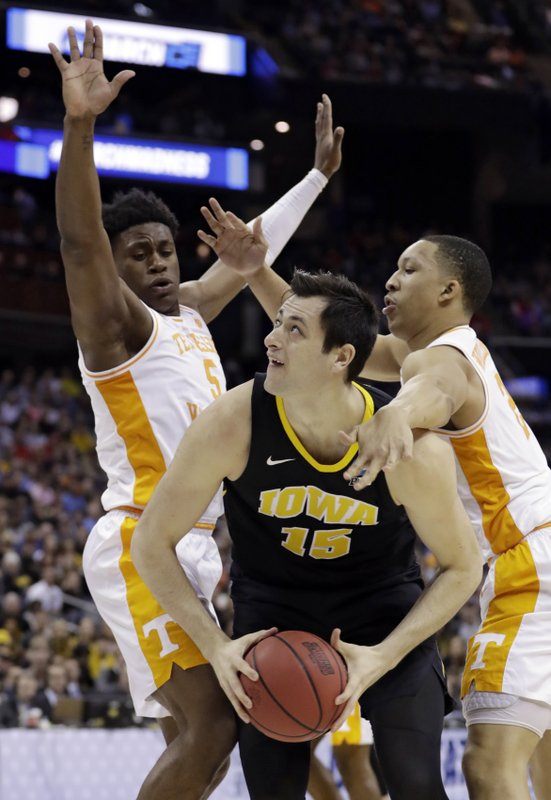 Iowa's Ryan Kriener, center, drives between Tennessee's Admiral Schofield, left, and Grant Williams in the first half during a second round men's college basketball game in the NCAA Tournament in Columbus, Ohio, Sunday, March 24, 2019. (AP Photo/Tony Dejak)