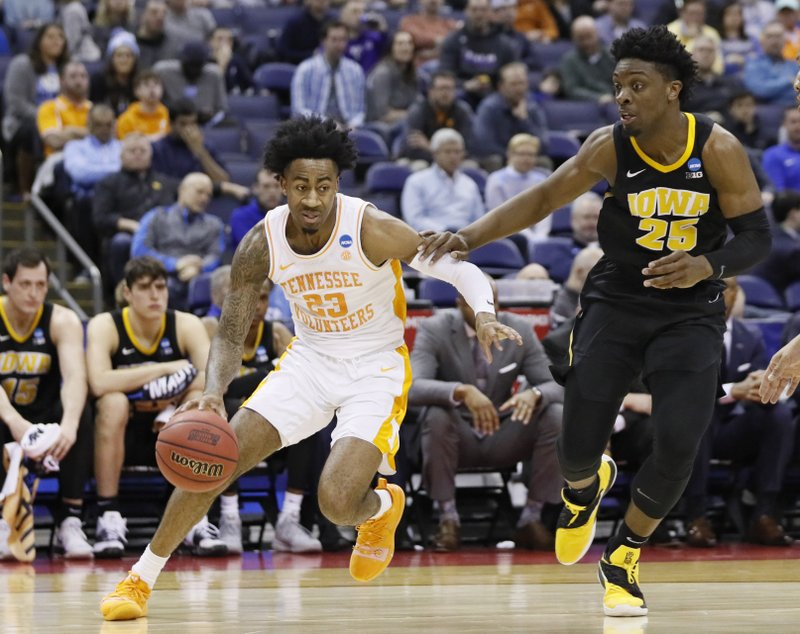 Tennessee's Jordan Bowden (23) drives past Iowa's Tyler Cook (25) in the first half during a second round men's college basketball game in the NCAA Tournament in Columbus, Ohio, Sunday, March 24, 2019. (AP Photo/John Minchillo)