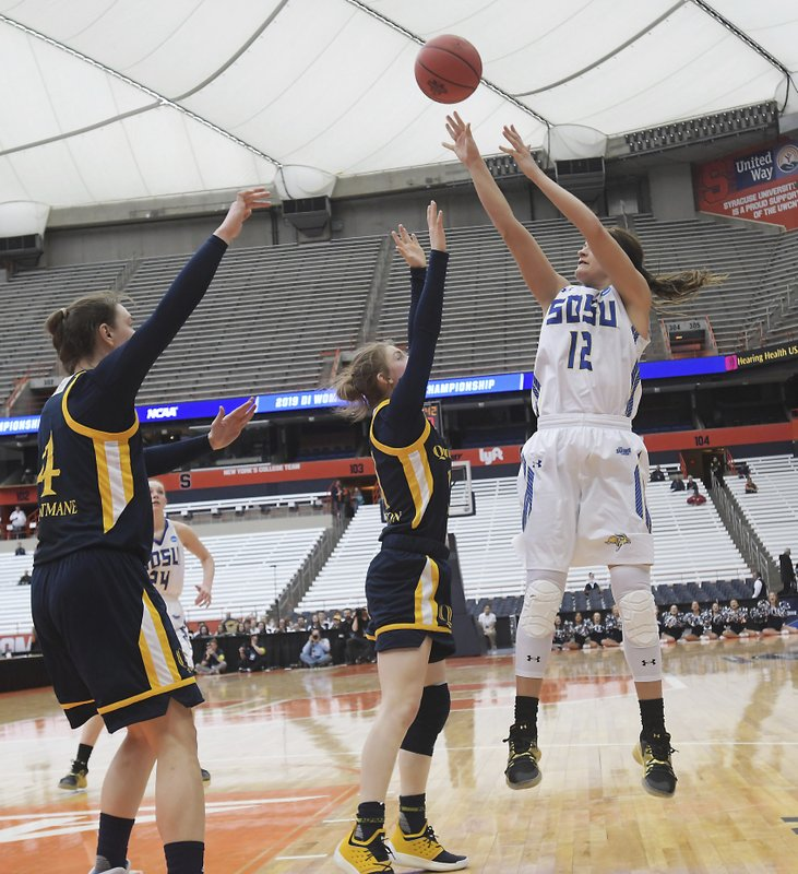 South Dakota State's Macy Miller (12) shoots over Quinnipiac's Edel Thornton, center, and Paula Straumane during of a first-round game in the NCAA women's college basketball tournament in Syracuse, N. (AP Photo/Heather Ainsworth)