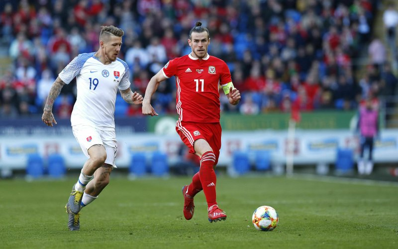 Slovakia's Juraj Kucka, left, and Wales' Gareth Bale battle for the ball during the Euro 2020 qualifying, Group E soccer match at the Cardiff City Stadium, Wales, Sunday March 24, 2019. (Darren Staples/PA via AP)