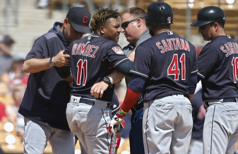 Cleveland Indians' Jose Ramirez (11) is helped to his feet after an injury during the third inning of the team's spring training baseball game against the Chicago White Sox on Sunday, March 24, 2019, in Glendale, Ariz. (41) and third base coach Mike Sarbaugh (16). (AP Photo/Sue Ogrocki)