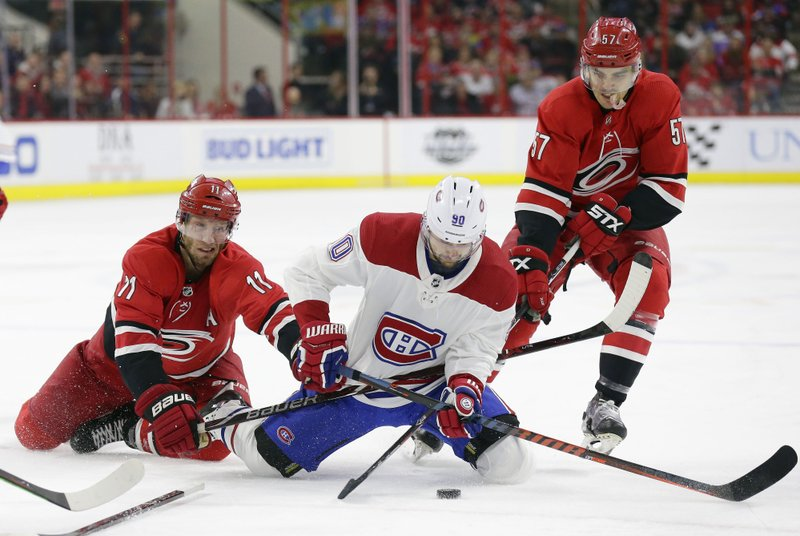 Carolina Hurricanes' Jordan Staal (11) and Trevor van Riemsdyk (57) skate for the puck with Montreal Canadiens' Tomas Tatar (90), of Slovakia, during the second period of an NHL hockey game in Raleigh, N. (AP Photo/Gerry Broome)