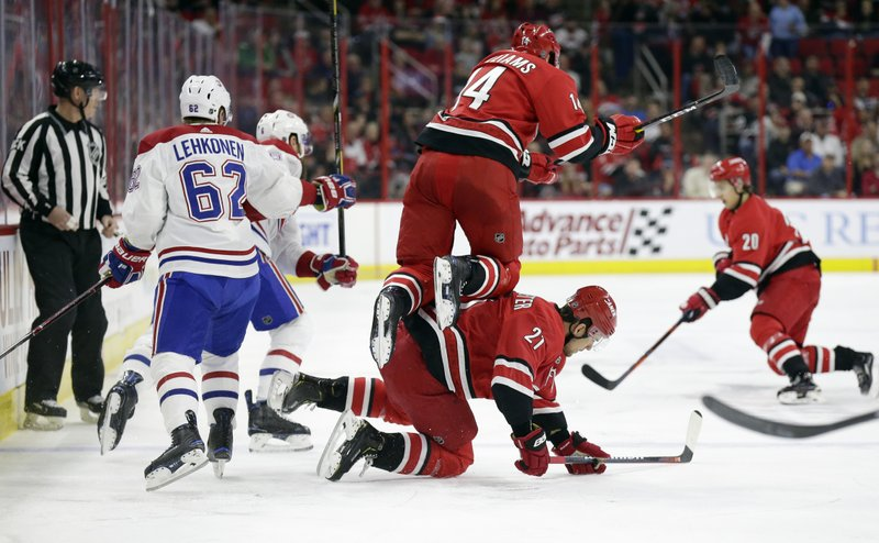 Carolina Hurricanes' Justin Williams (14) jumps over teammate Nino Niederreiter (21), of the Czech Republic, while Montreal Canadiens' Artturi Lehkonen (62), of Finland, chases the puck during the first period of an NHL hockey game in Raleigh, N. (AP Photo/Gerry Broome)