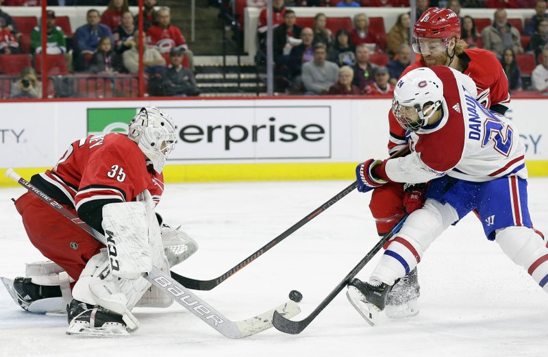 Montreal Canadiens' Phillip Danault (24) tries to score against Carolina Hurricanes goalie Curtis McElhinney (35) while Hurricanes' Dougie Hamilton (19) defends during the second period of an NHL hockey game in Raleigh, N. (AP Photo/Gerry Broome)