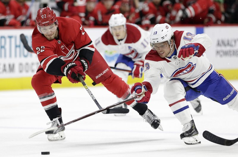 Carolina Hurricanes' Brett Pesce (22) and Montreal Canadiens' Max Domi (13) chase the puck during the second period of an NHL hockey game in Raleigh, N. (AP Photo/Gerry Broome)