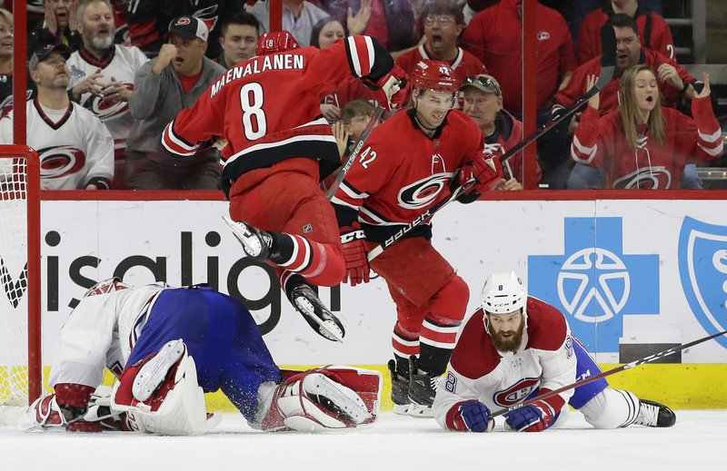 Carolina Hurricanes' Saku Maenalanen (8), of Finland, jumps over Montreal Canadiens goalie Carey Price while Hurricanes' Greg McKegg (42) looks on and Canadiens' Jordie Benn (8) falls during the first period of an NHL hockey game in Raleigh, N. (AP Photo/Gerry Broome)