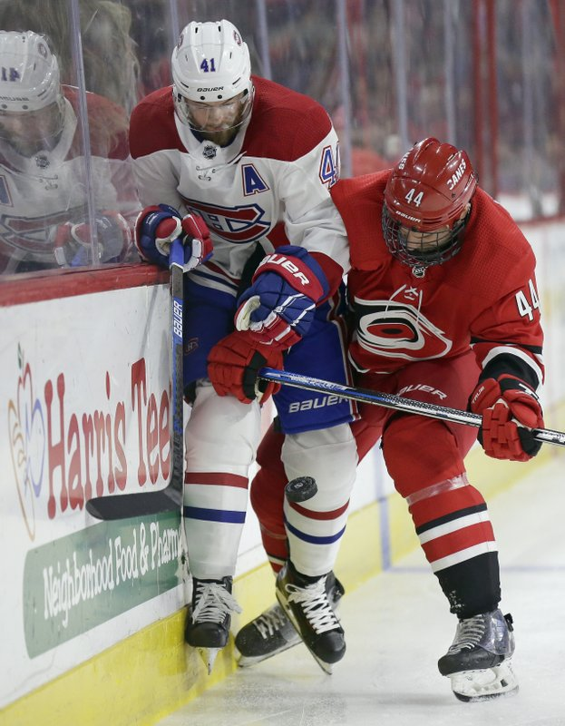 Montreal Canadiens' Paul Byron (41) and Carolina Hurricanes' Calvin de Haan (44) chase the puck during the first period of an NHL hockey game in Raleigh, N. (AP Photo/Gerry Broome)