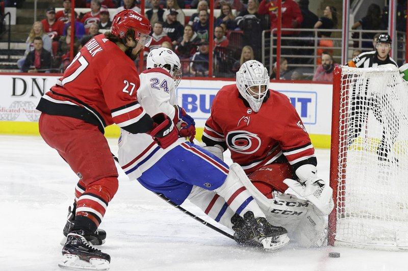 Carolina Hurricanes' Justin Faulk (27) and goalie Curtis McElhinney defend against Montreal Canadiens' Phillip Danault (24) during the first period of an NHL hockey game in Raleigh, N. (AP Photo/Gerry Broome)