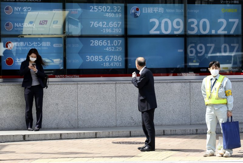 A man looks at an electronic stock board of a securities firm in Tokyo, Monday, March 25, 2019. Shares were sharply lower in Asia on Monday after Wall Street ended last week with a broad retreat. (AP Photo/Koji Sasahara)
