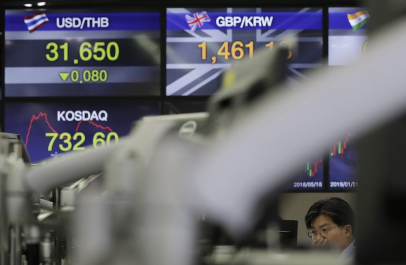 A currency trader watches the computer monitors near the screens showing the foreign exchange rates at the foreign exchange dealing room in Seoul, South Korea, Monday, March 25, 2019. (AP Photo/Lee Jin-man)