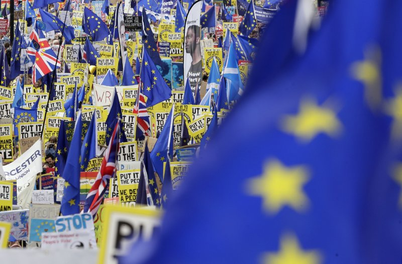 Demonstrators carry posters and flags during a Peoples Vote anti-Brexit march in London, Saturday, March 23, 2019. (AP Photo/Tim Ireland)