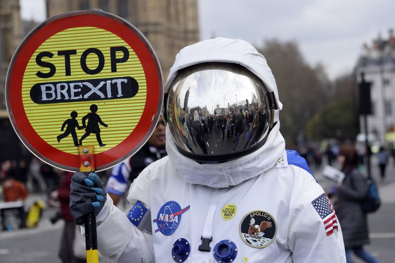 A demonstrator in an astronaut suit carries a sign during a Peoples Vote anti-Brexit march in London, Saturday, March 23, 2019. (AP Photo/Kirsty Wigglesworth)