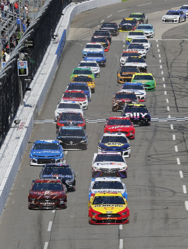 Joey Logano (22) leads the field at the start of a NASCAR Cup Series auto race at Martinsville Speedway in Martinsville, Va. (AP Photo/Steve Helber)