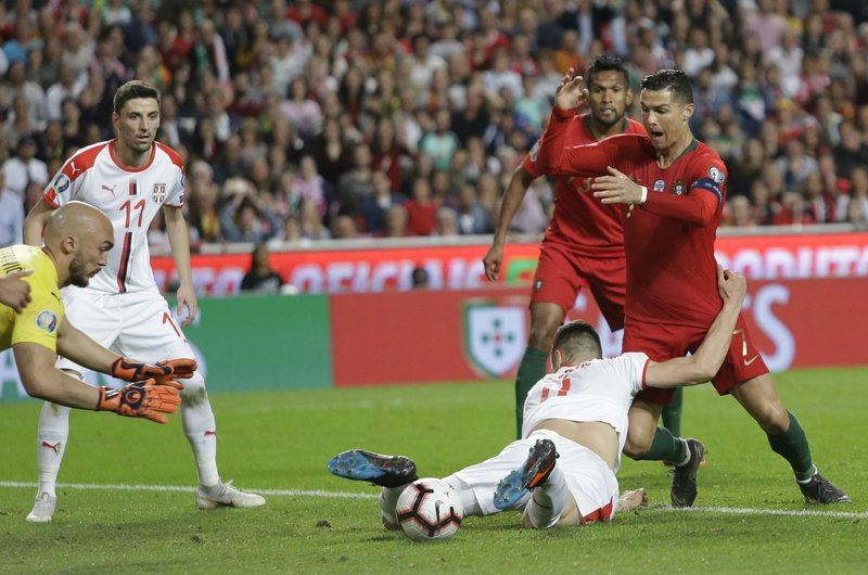Serbia's Nikola Milenkovic, bottom, and Portugal's Cristiano Ronaldo challenge for the ball during the Euro 2020 group B qualifying soccer match between Portugal and Serbia at the Luz stadium in Lisbon, Portugal, Monday, March 25, 2019. (AP Photo/Armando Franca)