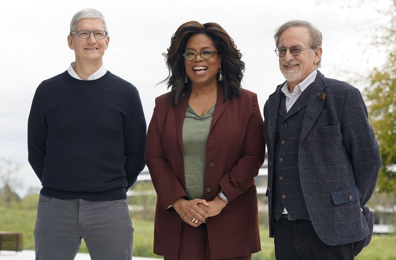 From left, Apple CEO Tim Cook, Oprah Winfrey and Steven Spielberg pose for a photo outside the Steve Jobs Theater during an event to announce new Apple products Monday, March 25, 2019, in Cupertino, Calif. (AP Photo/Tony Avelar)