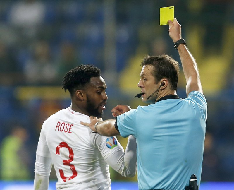 Referee Aleksei Kulbakov of Belarus shows a yellow card to England's Danny Rose during the Euro 2020 group A qualifying soccer match between Montenegro and England at the City Stadium in Podgorica, Montenegro, Monday, March 25, 2019. (AP Photo/Darko Vojinovic)