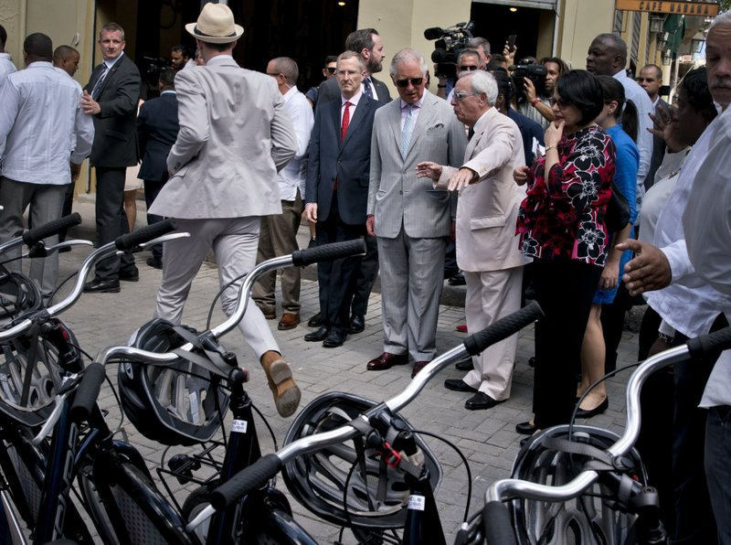 Britain's Prince Charles, the Prince of Wales, top center right, wearing sunglasses, takes a guided tour by City Historian Eusebio Leal, pointing, in the historical center of Havana, Cuba, Monday, March 25, 2019. (AP Photo/Ramon Espinosa)