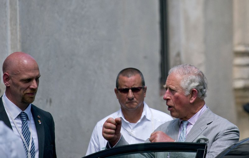 Britain's Prince Charles, the Prince of Wales, holds up his fists as he talks with one of his bodyguards after visiting a gym boxing during his official trip to Cuba, in Havana, Cuba, Sunday, March 24, 2019. (AP Photo/Ramon Espinosa)