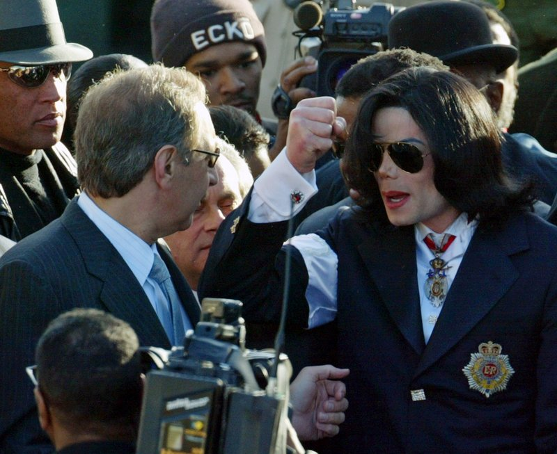 File - In this Jan. 16, 2004 file photo, Michael Jackson looks for his umbrella as he talks to his defense attorney Mark Geragos, left, as they arrive at the courthouse in Santa Maria, Calif. (AP Photo/Spencer Weiner, pool, file)