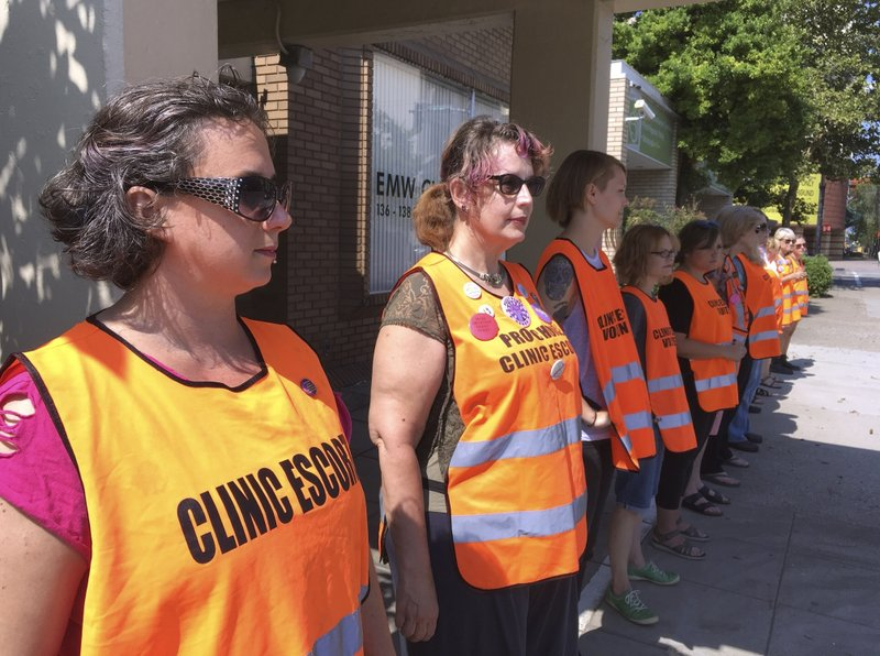 FILE - In this July 17, 2017 file photo, escort volunteers line up outside the EMW Women's Surgical Center in Louisville, Ky. (AP Photo/Dylan Lovan, File)