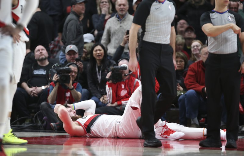 Portland Trail Blazers center Jusuf Nurkic, on ground, was injured and left the court on a stretcher as the Blazers beat the Brooklyn Nets in double overtime, 148-144, during an NBA basketball game in Portland, Ore. (AP Photo/Randy L. Rasmussen)