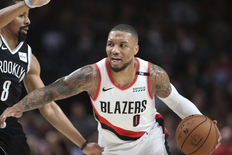 Brooklyn Nets guard Spencer Dinwiddie, left, defends against Portland Trail Blazers guard Damian Lillard during the first half of an NBA basketball game in Portland, Ore. (AP Photo/Randy L. Rasmussen)