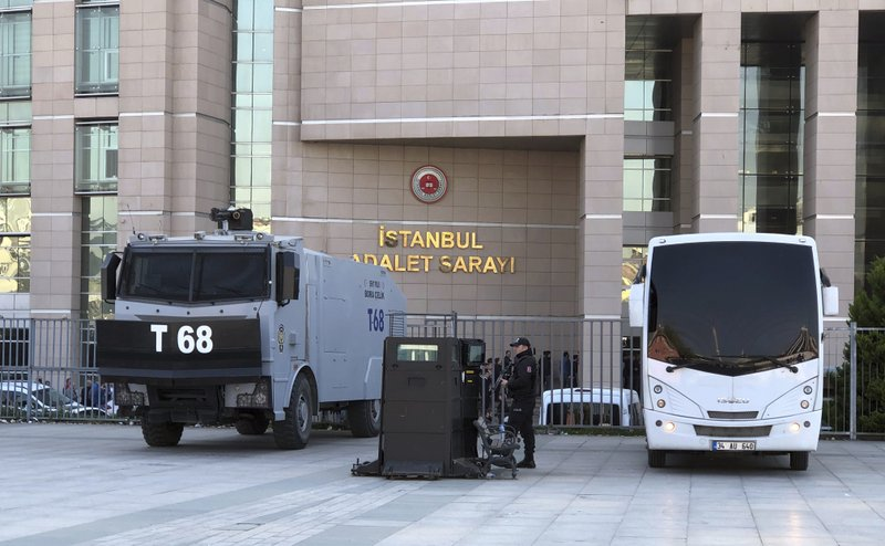 Security cars and an official stand outside the Justice Palace as a trial against Metin Topuz, a Turkish employee of the United States Consulate in Istanbul charged with espionage and attempting to overthrow the Turkish government, began in Istanbul, Tuesday, March 26, 2019. (AP Photo/Mehet Guzel)