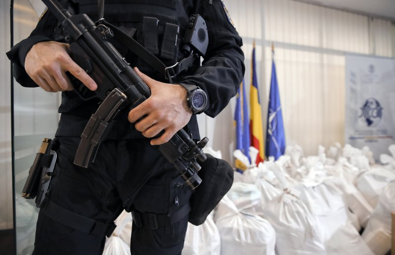 A Romanian special police officer guards bags of cocaine inside the building of the Directorate for Investigating Organized Crime and Terrorism in Bucharest, Romania, Tuesday, March 26, 2019. (338 million USD) from a capsized boat in the Danube Delta. (AP Photo/Vadim Ghirda)