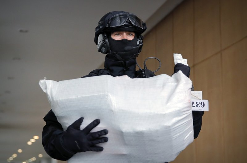 A Romanian special police officer carries a bag of cocaine outside the building of the Directorate for Investigating Organized Crime and Terrorism in Bucharest, Romania, Tuesday, March 26, 2019. (338 million USD) from a capsized boat in the Danube Delta. (AP Photo/Vadim Ghirda)