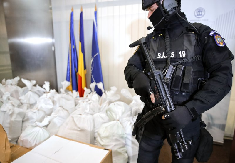 A Romanian special police officer guards bags of cocaine inside the building of the Directorate for Investigating Organized Crime and Terrorism, in Bucharest, Romania, Tuesday, March 26, 2019. (338 million USD) from a capsized boat in the Danube Delta. (AP Photo/Vadim Ghirda)