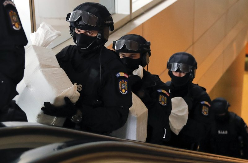 Romanian special police troops carry bags of cocaine inside the building of the Directorate for Investigating Organized Crime and Terrorism in Bucharest, Romania, Tuesday, March 26, 2019. (338 million USD) from a capsized boat in the Danube Delta. (AP Photo/Vadim Ghirda)