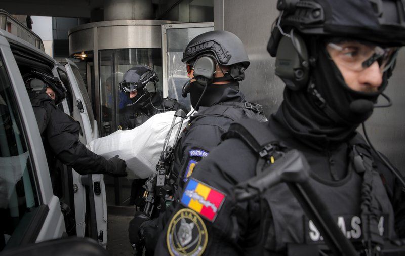 Romanian special police troops carry bags of cocaine outside the building of the Directorate for Investigating Organized Crime and Terrorism in Bucharest, Romania, Tuesday, March 26, 2019. (338 million USD) from a capsized boat in the Danube Delta. (AP Photo/Vadim Ghirda)