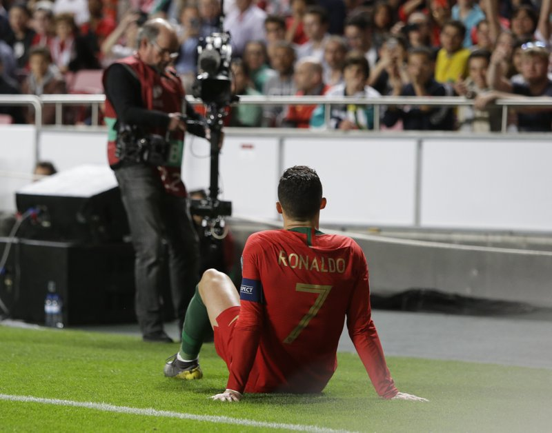 Portugal's Cristiano Ronaldo sits on the pitch after getting injured during the Euro 2020 group B qualifying soccer match between Portugal and Serbia at the Luz stadium in Lisbon, Portugal, Monday, March 25, 2019. (AP Photo/Armando Franca)
