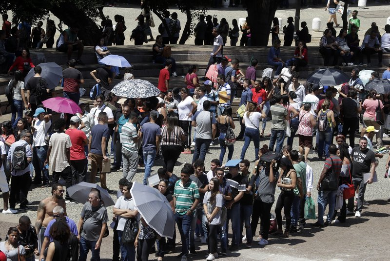 Unemployed line up  to attend a job fair organized by the local government and a trade union, in downtown Sao Paulo, Brazil, Tuesday, March 26, 2019. (AP Photo/Andre Penner)