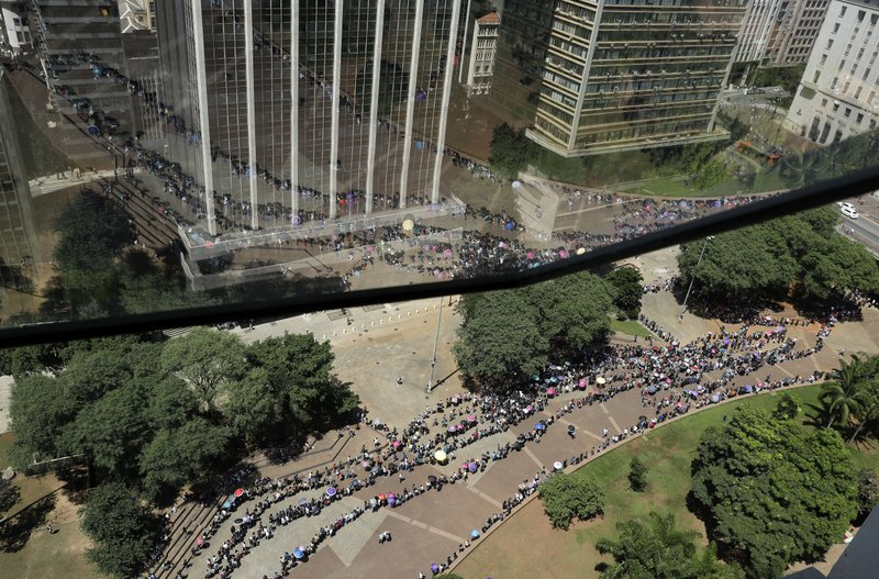 Unemployed line up  to attend a job fair in downtown Sao Paulo, Brazil, Tuesday, March 26, 2019. The Getulio Vargas Foundation think tank published a study on Monday saying the average growth of the Brazilian economy between 2011 and 2020 could to be the worst since it started measuring in 1901, at 0. (AP Photo/Andre Penner)