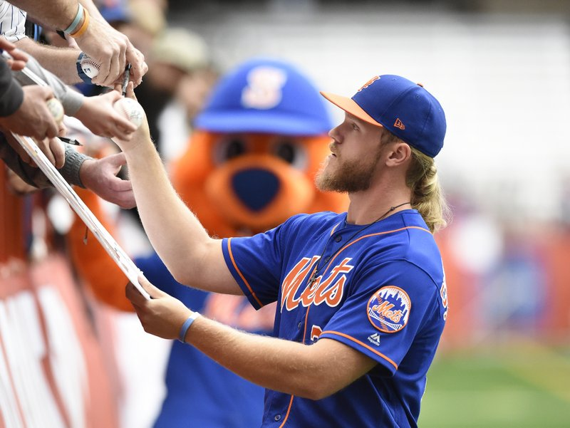 New York Met pitcher Noah Syndergaard signs autographs. The Mets worked out at the Carrier Dome in Syracuse, N. (Dennis Nett/The Post-Standard via AP)