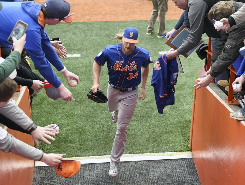 New York Mets pitcher Noah Syndergaard runs into the locker room after a workout at the Carrier Dome in Syracuse, N. (Dennis Nett/The Post-Standard via AP)