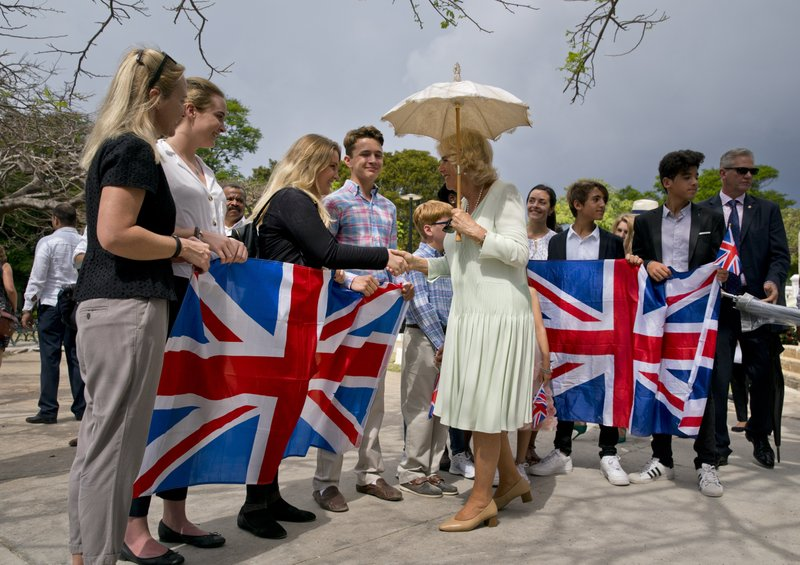 Camilla, Duchess of Cornwall, greets a group of people holding United Kingdom's national flags during a cultural event in Havana, Cuba, Tuesday, March 26, 2019. (AP Photo/Ramon Espinosa)