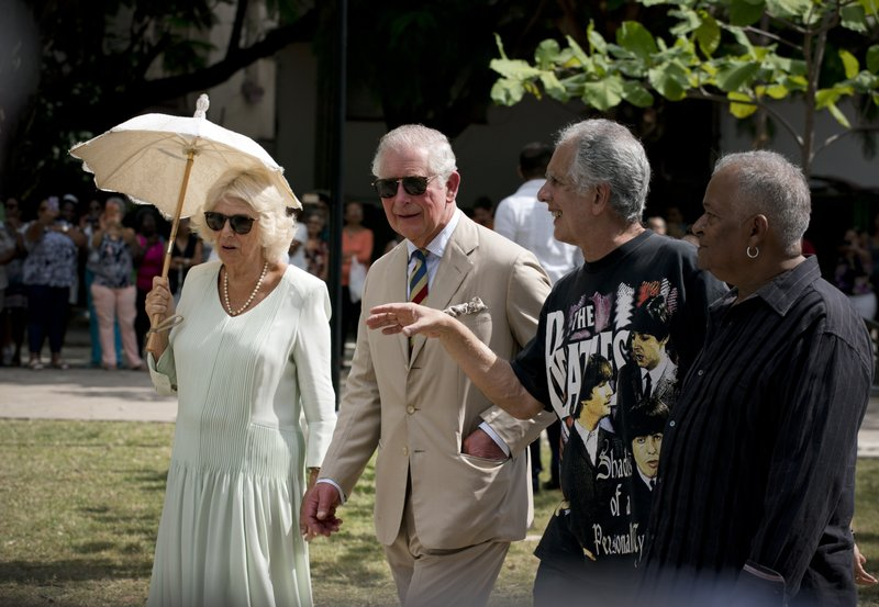 Prince Charles and his wife Camilla, Duchess of Cornwall, walk with journalist and Beatles' fan Guille Villar during a visit to  John Lennon Park, in Havana, Cuba, Tuesday, March 26, 2019. (AP Photo/Ramon Espinosa)
