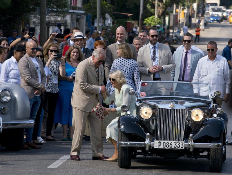 Prince Charles helps his wife Camilla, Duchess of Cornwall, out of a vintage car during a cultural event in Havana, Cuba, Tuesday, March 26, 2019. (AP Photo/Ramon Espinosa)