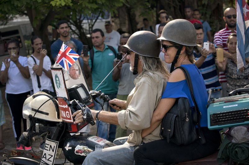 A couple ride on an English motorcycle adorned with images of Che Guevara and Fidel Castro as people gather for the arrival of Prince Charles and his wife Camilla, Duchess of Cornwall, in Havana, Cuba, Tuesday, March 26, 2019. (AP Photo/Ramon Espinosa)