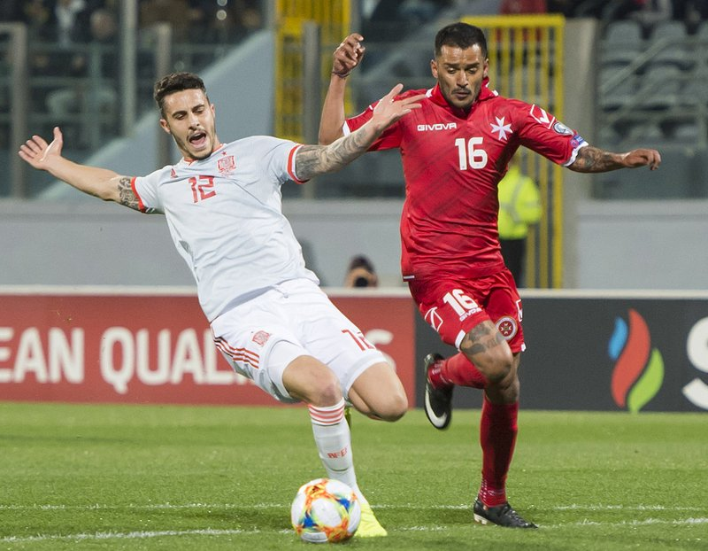 Malta's John Mintoff, right, and Spain's Mario Hermoso vie for the ball during the Euro 2020 group F qualifying soccer match between Malta and Spain at the national stadium Ta Qali Malta, Tuesday, March 26, 2019. (AP Photo/Rene Rossignaud)