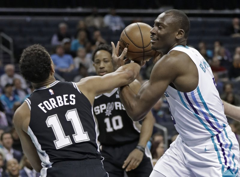Charlotte Hornets' Bismack Biyombo, right, is fouled by San Antonio Spurs' Bryn Forbes, left, during the first half of an NBA basketball game in Charlotte, N. (AP Photo/Chuck Burton)