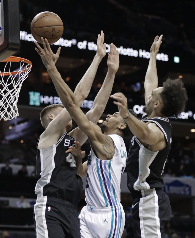 Charlotte Hornets' Jeremy Lamb, center, drives between San Antonio Spurs' Davis Bertans, left, and Derrick White, right, during the first half of an NBA basketball game in Charlotte, N. (AP Photo/Chuck Burton)