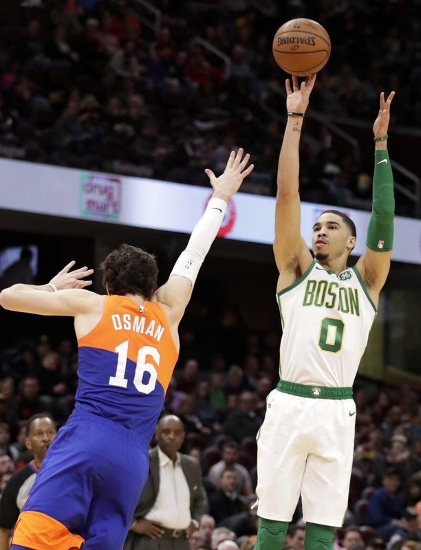 Boston Celtics' Jayson Tatum (0) shoots over Cleveland Cavaliers' Cedi Osman (16) in the first half of an NBA basketball game, Tuesday, March 26, 2019, in Cleveland. (AP Photo/Tony Dejak)