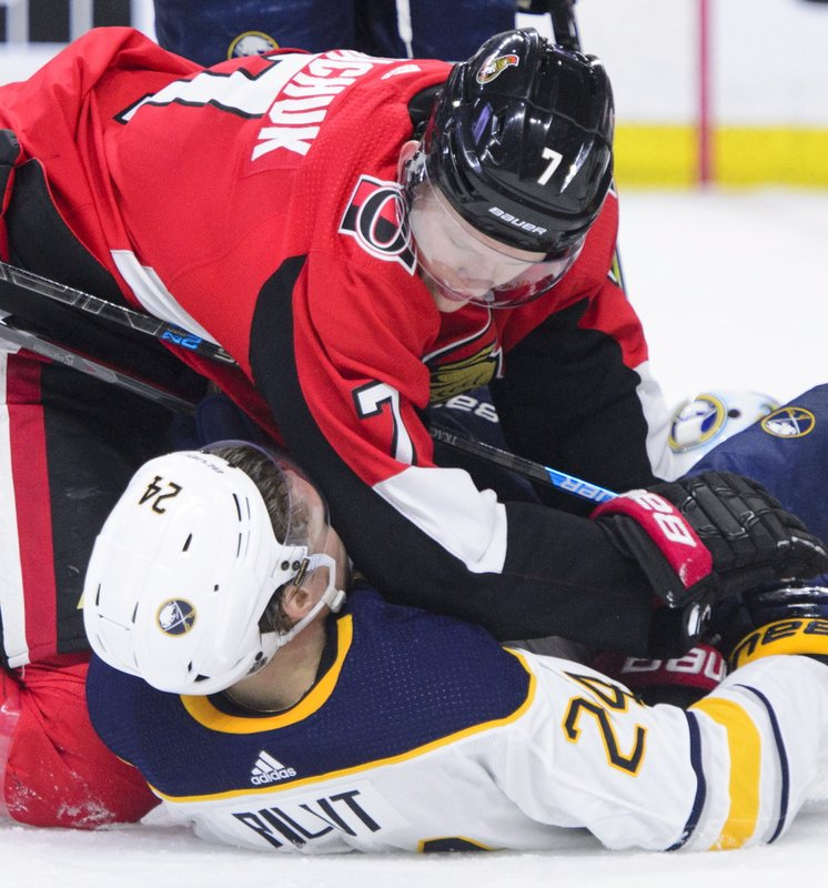 Ottawa Senators left wing Brady Tkachuk (7) gives Buffalo Sabres defenseman Lawrence Pilut (24) a little scrubbing during first period NHL hockey action in Ottawa, Ontario, on Tuesday, March 26, 2019. (Sean Kilpatrick/The Canadian Press via AP)